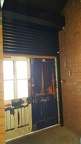 The new roller shutter is installed behind the front doors, and is tested in situ.