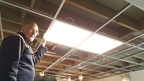 Let there be light! (1) - GWS electrician David Brown test fits the first LED fitment to the Panel Room suspended ceiling.